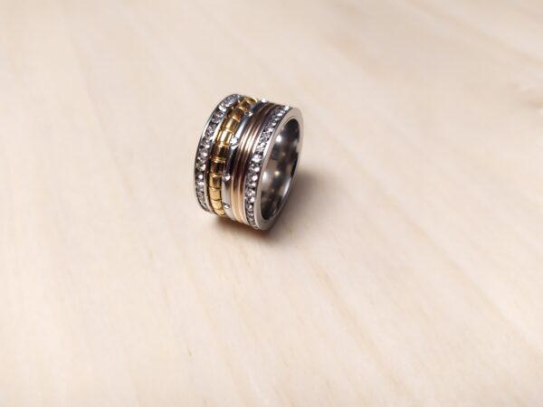 Anel em aço com uma fila de brilhantes nas pontas, uma fila rose gold, uma fila dourada e a do meio prateada com brilhantes