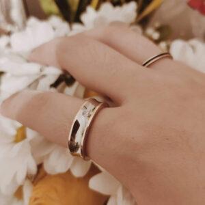 Anel em aço prateado com dourado nas pontas e brilhante ao centro