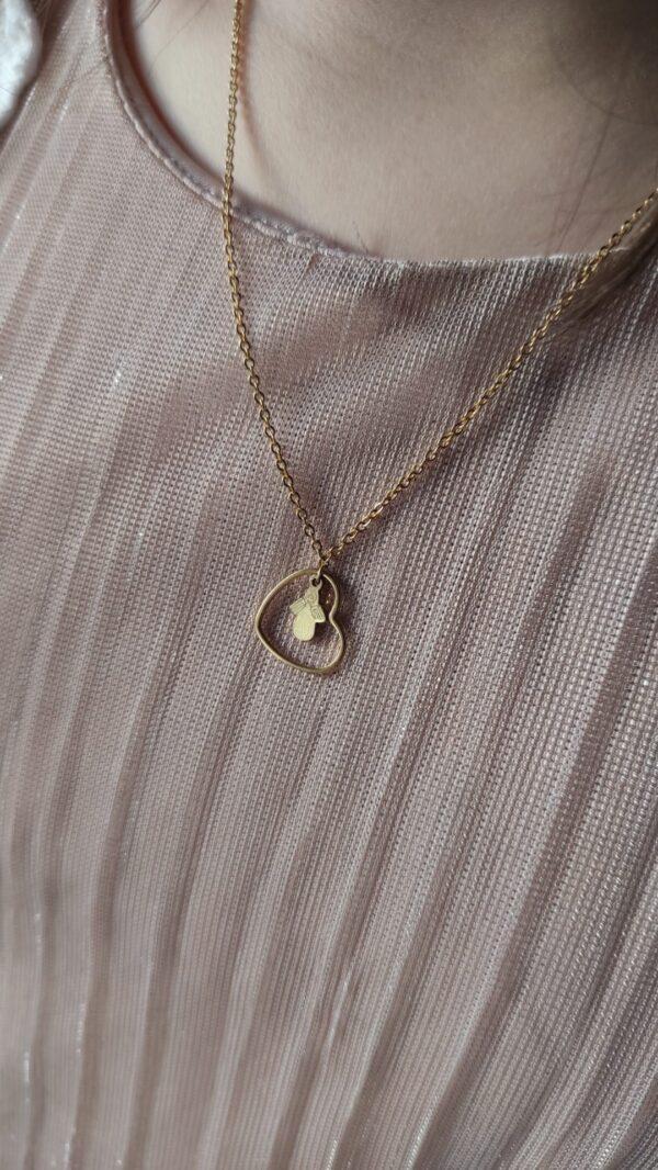 Colar com fio em aço com pendente em forma de coração com pequeno anjo também em aço