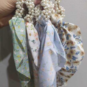 Elástico com pérolas e tecido azul claro com flores brancas e laranja